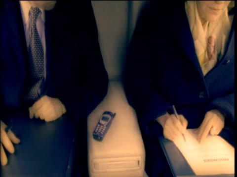 vídeos y material grabado en eventos de stock de man and woman seated on plane check and amend business reports - t mobile