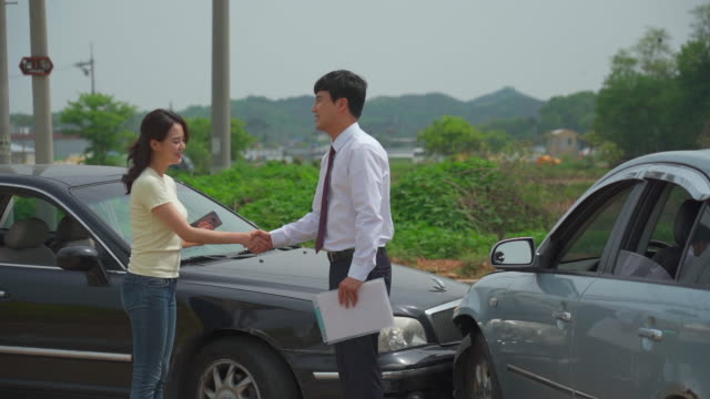 man and woman shaking hands after a car accident - 和解点の映像素材/bロール