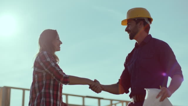 Man and woman shaking hands with construction site in background