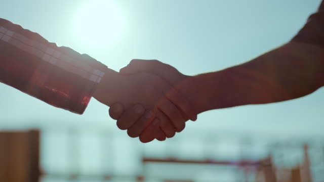 man and woman shaking hands with construction site in background - handshake stock videos and b-roll footage