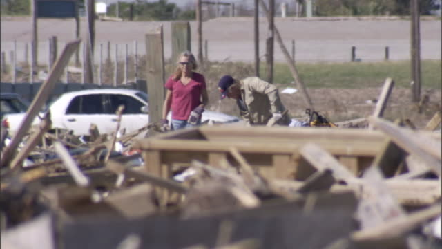 a man and woman shovel and dig out hurricane debris. - pulizia dell'ambiente video stock e b–roll