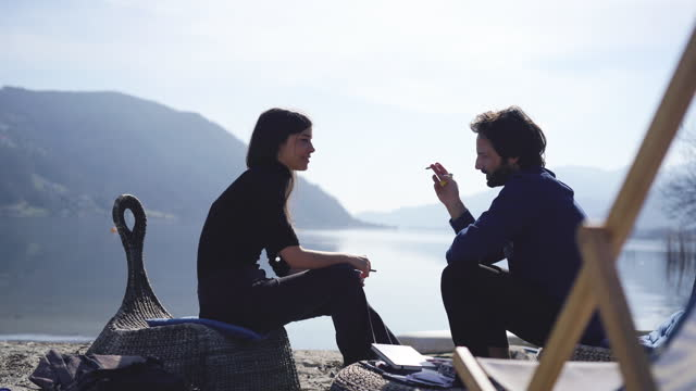 man and woman sit on beach smoking a cigarette or joint - casual clothing stock videos & royalty-free footage