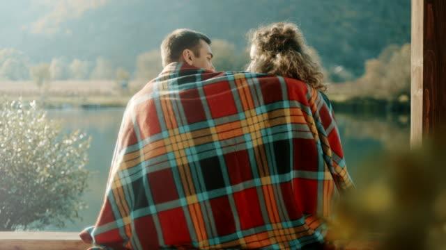 vidéos et rushes de homme et femme assise au bord lac sous couverture - assis