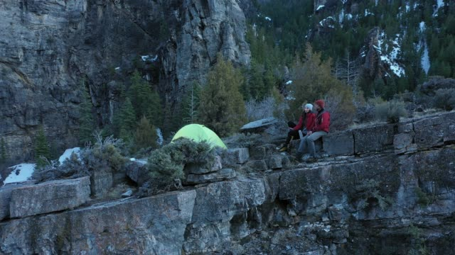 man and woman sitting in camp on top of cliff at dusk - american fork canyon点の映像素材/bロール