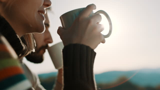 man and woman sitting in front of the tent and drinking coffee on camping trip on the mountain - love emotion stock videos and b-roll footage