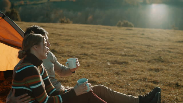 man and woman sitting in front of the tent and drinking coffee on camping trip on the mountain - campeggiare video stock e b–roll