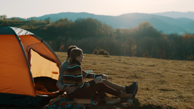 man and woman sitting in front of the tent and drinking coffee on camping trip on the mountain - tenda da campeggio video stock e b–roll