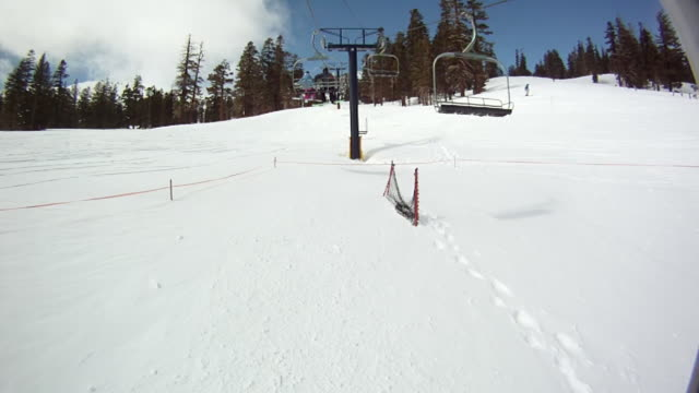 WS  PAN POV Man and woman sitting in ski lift  / Mammoth Lakes, California, United States