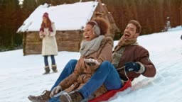 SLO MO Man and woman sitting on a sledge sliding down the hill after being pushed by a male friend