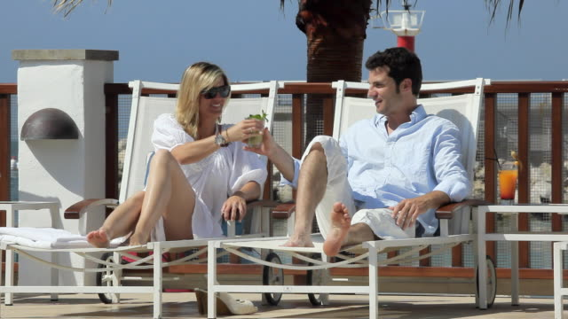 WS Man and woman sitting on deckchairs, taking drink / Port de Soller, Mallorca, Baleares, Spain