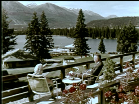 vídeos y material grabado en eventos de stock de ws man and woman sitting on terrace of building, jasper, canada / audio - jasper