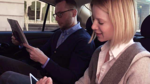 man and woman sitting together in back seat at car, daytime - seat stock videos & royalty-free footage