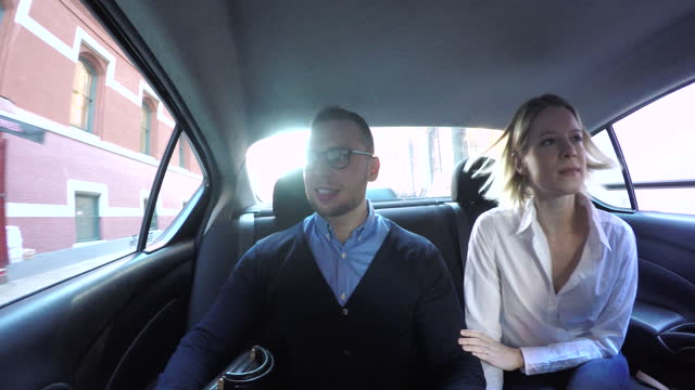 man and woman sitting together in back seat at car, daytime - passenger seat stock videos & royalty-free footage