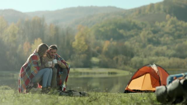 stockvideo's en b-roll-footage met man en vrouw zitten met deken op hun rug en drinken koffie op het kamperen reis aan het meer - tent