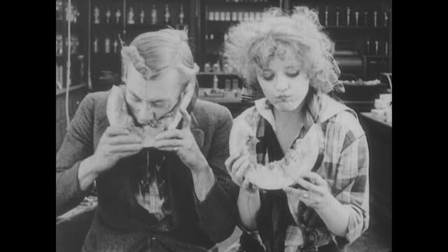 1917 a man (al st. john) and woman (alice mann) sloppily eat large wedges of watermelon - hungrig stock-videos und b-roll-filmmaterial