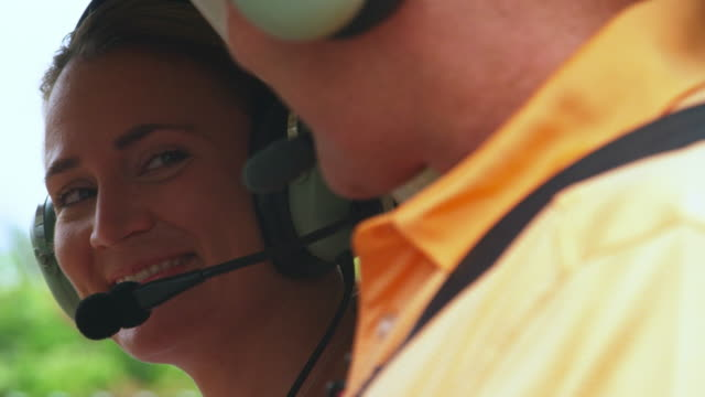 man and woman smile at each other before taking off in helicopter - helicopter tour stock videos and b-roll footage