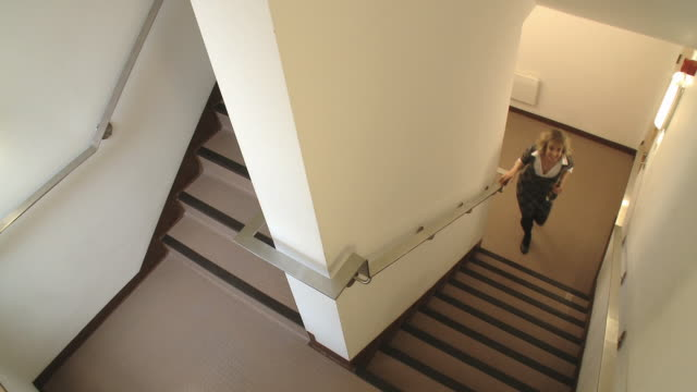 vidéos et rushes de hs ws security camera pov man and woman sneaking up stairwell together during office party/ london, england - staircase