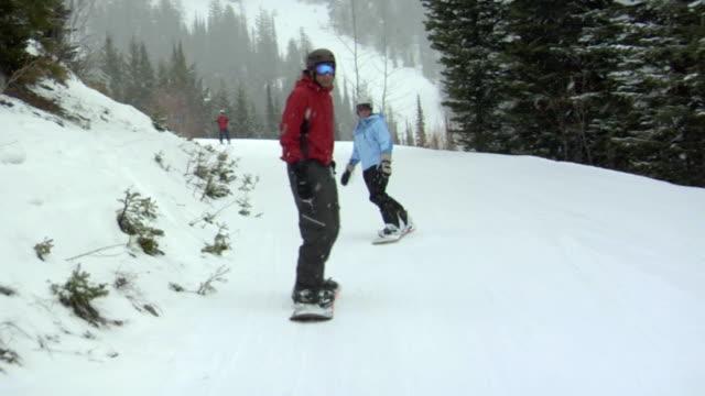 vídeos de stock e filmes b-roll de slo mo, ms, man and woman snowboarding, whitefish, montana, usa - roupa de esqui