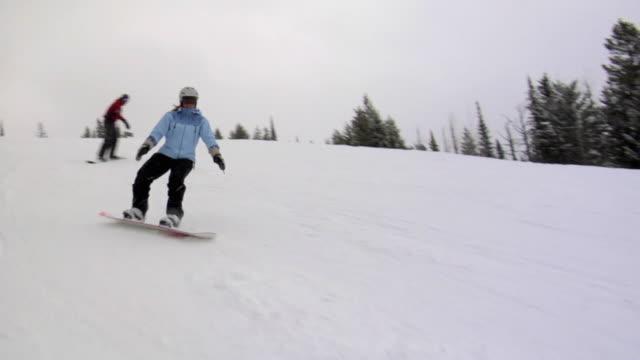 vídeos de stock e filmes b-roll de ws, shaky, man and woman snowboarding, whitefish, montana, usa - snowboard