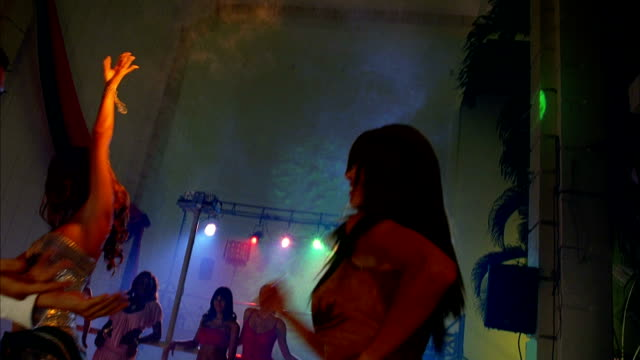 A man and woman spin each other around as they enjoy salsa dancing in a nightclub. Available in HD.