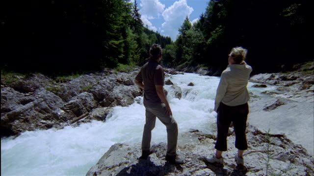 a man and woman stand on a rock near rapids of rissbach river in tyrol, austria. - 手をかざす点の映像素材/bロール