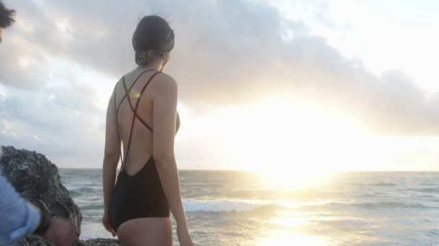 cu man and woman stand on rocks looking out to sea. - swimwear stock videos and b-roll footage