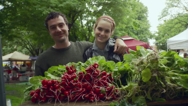 stockvideo's en b-roll-footage met ms man and woman standing behind vegetables and smiling / burlington, vermont, usa  - boer agrarisch beroep