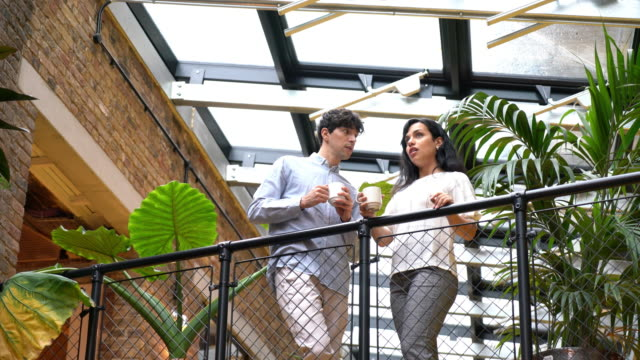 man and woman standing on balcony in office with cuts of coffee - businesswear stock videos & royalty-free footage