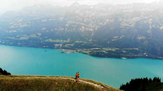 man and woman standing on the background of  mountains near  the lake - switzerland stock videos & royalty-free footage