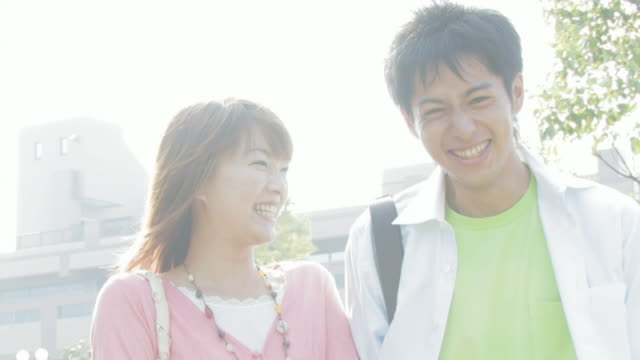 man and woman standing side by side smiling - 大学生点の映像素材/bロール
