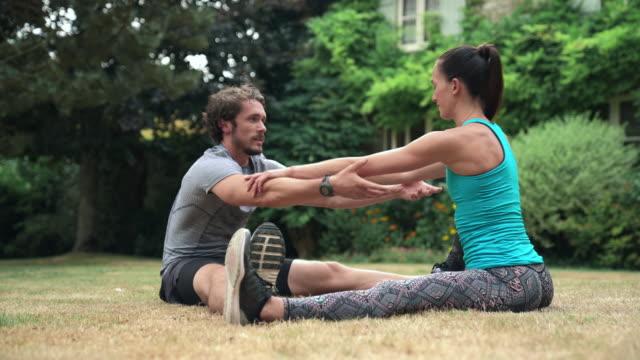 stockvideo's en b-roll-footage met man and woman stretching - benen gespreid