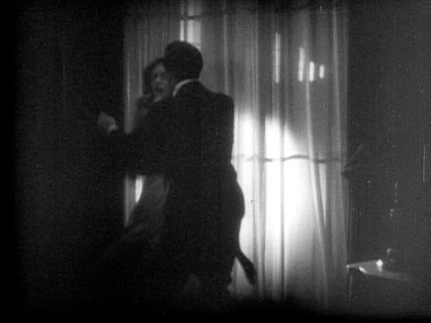 vidéos et rushes de ms, b&w, man and woman struggling in dark room, 1920's  - agression