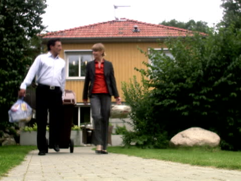 Man and woman taking out the garbage for recycling Sweden.