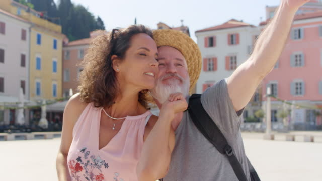 man and woman taking selfies in a town square on a sunny day - maglietta video stock e b–roll