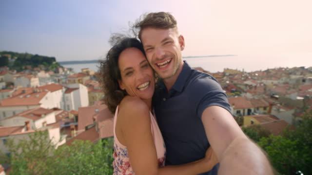 stockvideo's en b-roll-footage met man en vrouw nemen van selfies op een plek met uitzicht op een kustplaats hieronder - 45 49 jaar
