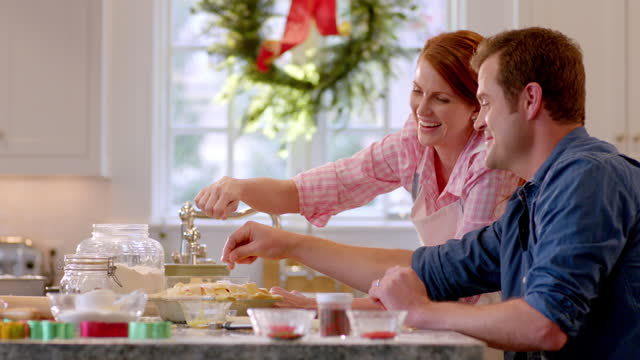 Man and woman talk and laugh while sprinkling sugar on lattice-top pie (dolly-shot)