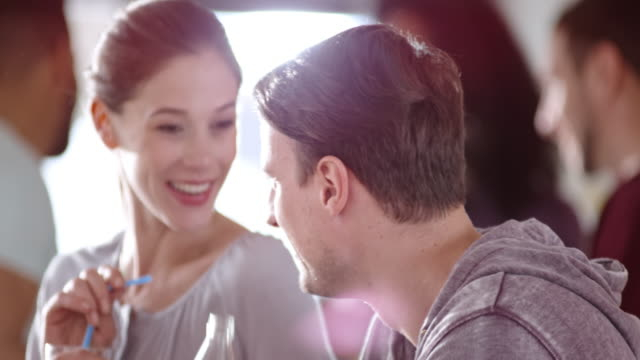 Man and woman talking and laughing at a party