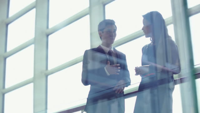 MS man and woman talking in a modern office with reflections in glass.