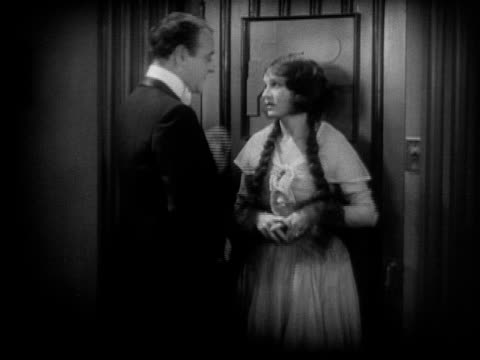 ms, b&w, man and woman talking in corridor, 1920's  - bianco e nero video stock e b–roll