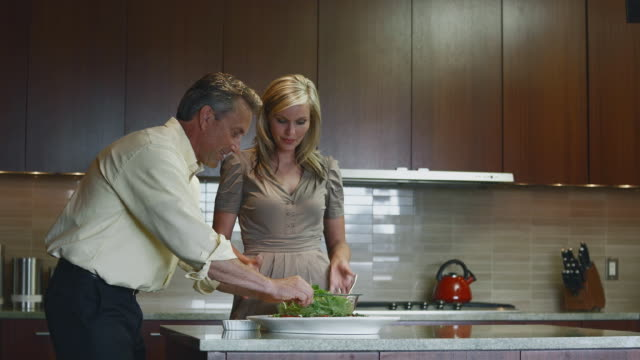 MS Man and woman talking in kitchen preparing salad and appetizers / Bellevue, Washington, USA
