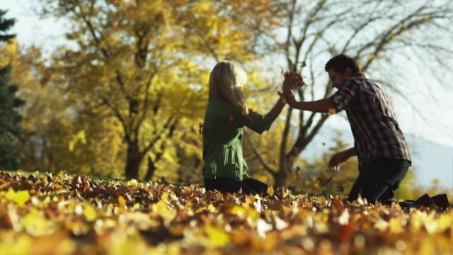 vídeos y material grabado en eventos de stock de ws slo mo man and woman throwing leaves at each other / provo, utah, usa - provo
