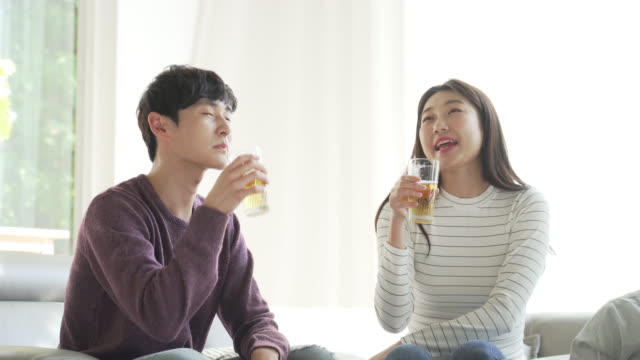 man and woman toasting a glass of beer on the sofa - east asia stock videos & royalty-free footage
