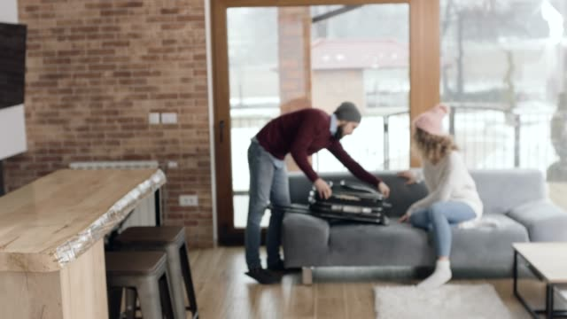 Man and woman unpacking suitcase at apartent on vacations