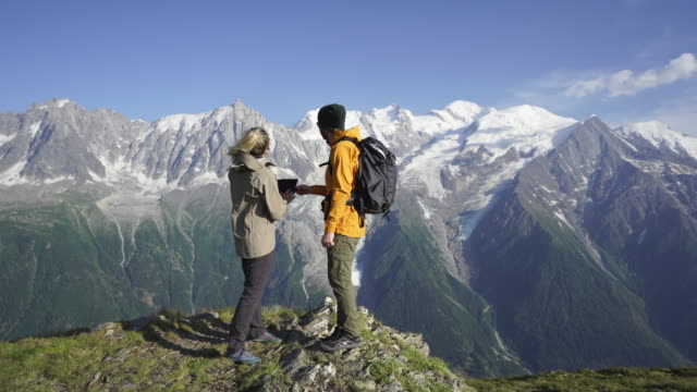 man and woman use tablet on mountain top, look out at view of mountains - generation z stock videos & royalty-free footage