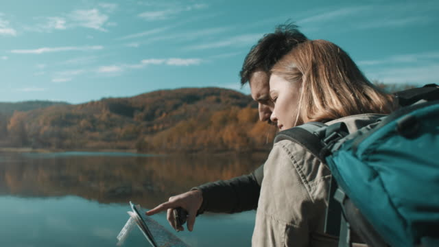 man and woman using map by the lake - named wilderness area stock videos & royalty-free footage