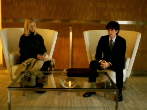 ws, man and woman waiting in lobby, new york city, new york, usa - anticipation点の映像素材/bロール