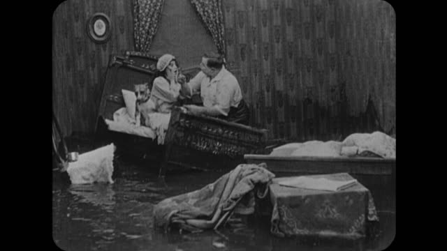 1916 man (fatty arbuckle) and woman (mabel normand) wake up to floating beds in waterlogged home - fatty arbuckle stock videos and b-roll footage