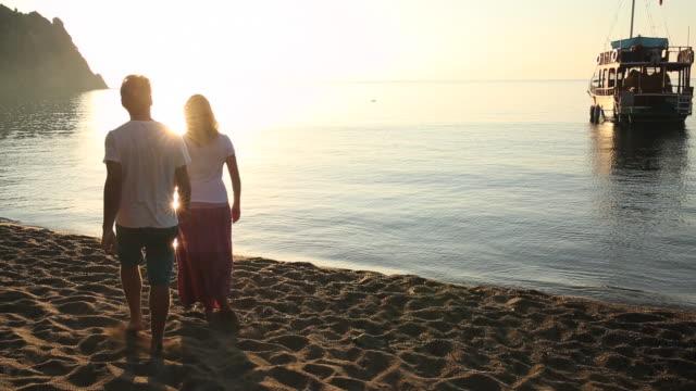vídeos y material grabado en eventos de stock de man and woman walk along beach edge at sunrise - falda