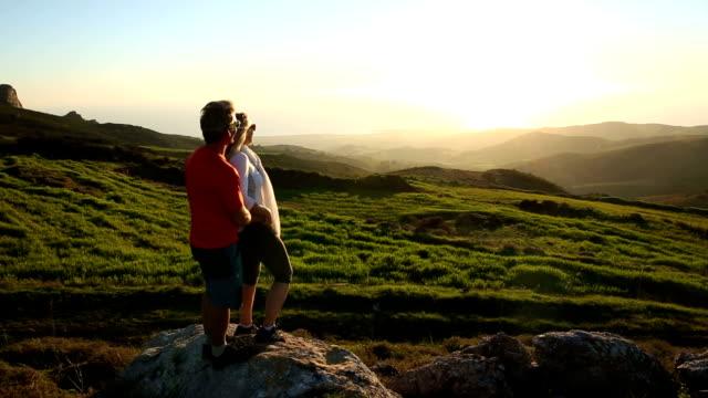 Mann und Frau gehen auf Gras-Wappen über hills