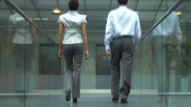 man and woman walking down glass office corridor, uk - nah stock-videos und b-roll-filmmaterial